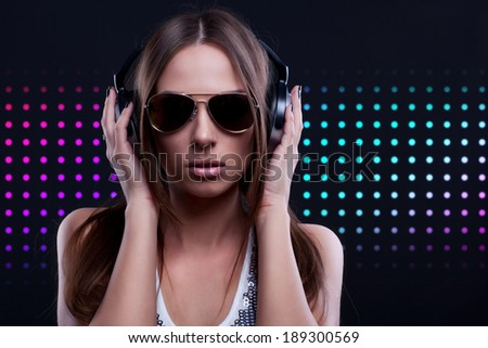 young DJ woman enjoying the music in the headphones wearing sunglasses - stock photo
