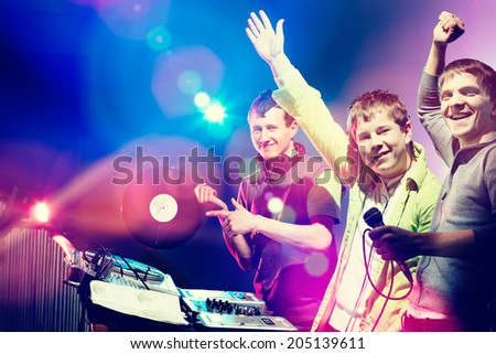 Young DJs playing records at a party in a nightclub. Looking at camera and smiling. - stock photo