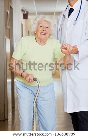 Young doctor assisting a senior woman to walk - stock photo
