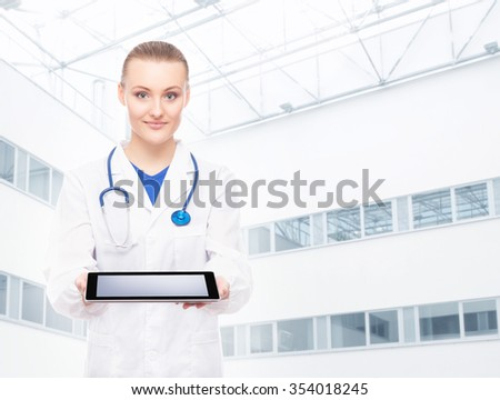 Young doctor being modern with a tablet over hospital building background.