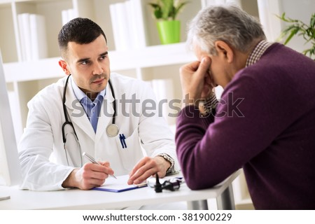 Young doctor carefully listening senior patient about his pains