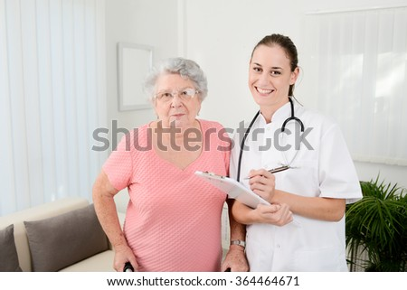 young doctor checking rehab medical progress to an elderly woman at home - stock photo