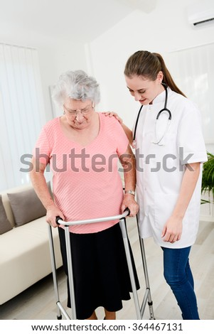 young doctor checking rehab medical progress to an elderly woman at home