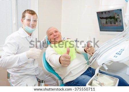 Young doctor dentist and old senior man patient showing thumb up, smiling and happy looking at the camera - stock photo