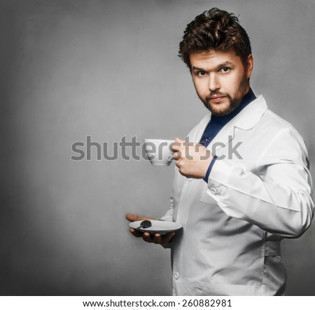 Young doctor drink tea coffee grey background - stock photo