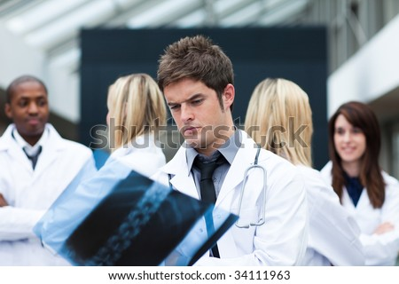 Young doctor examining an x-ray with his team in the background - stock photo