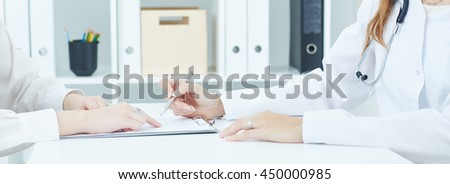 Young doctor explains how to fill out a medical form to female patient. Partnership, trust and medical ethics concept - stock photo
