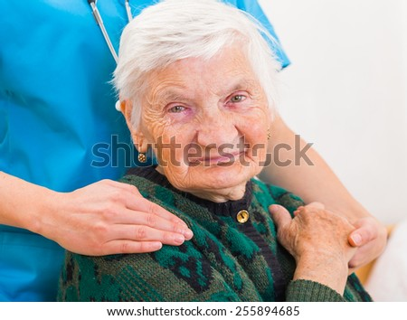 Young doctor giving helping hands for elderly woman