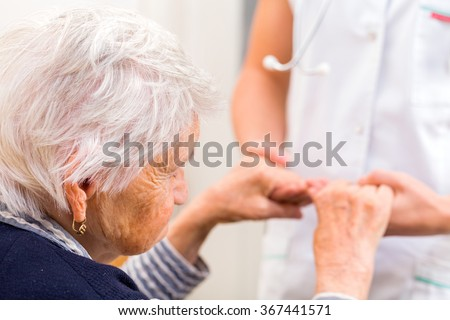 Young doctor giving helping hands for elderly woman - stock photo