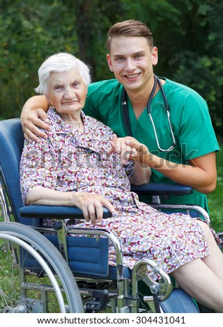 Young doctor helping a handicapped elderly woman - stock photo