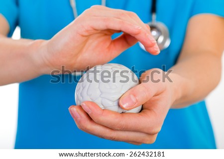 Young doctor holding a plastic brain in hands - stock photo