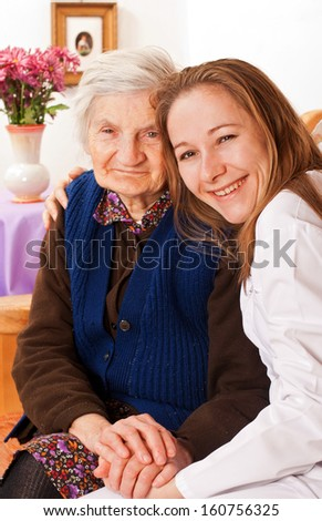Young doctor holds the old woman's hands - stock photo