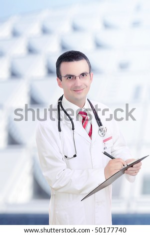 Young doctor(intern) outdoor, stand near the hospital building. Close-Up. - stock photo