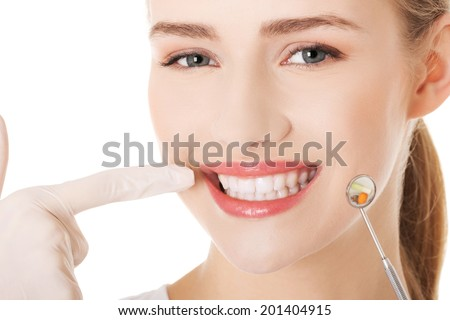 Young doctor or dentist with dental mirror and glove pointing on teeth. Isolated on white. - stock photo