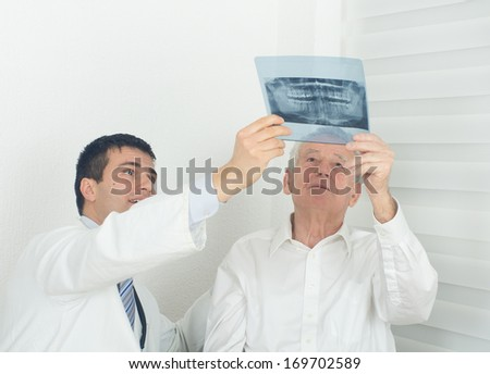 Young doctor showing a x-ray to senior patient - stock photo
