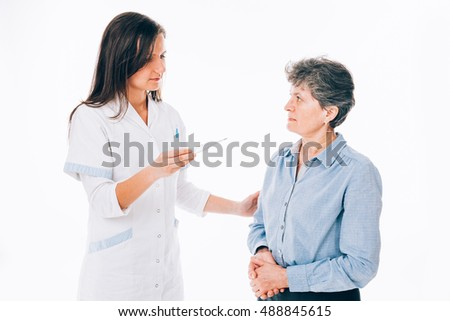 Young doctor shows a thermometer to her senior patient - isolated on white.
