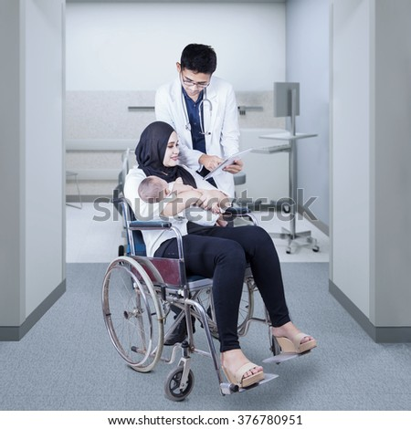 Young doctor speaking with his patient on the wheelchair while using digital tablet to explain at her