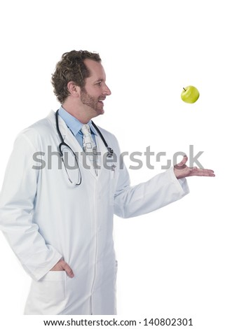 Young doctor tossing green apple against white background