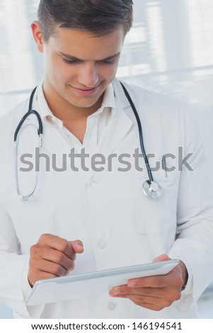 Young doctor using tablet in a bright hospital