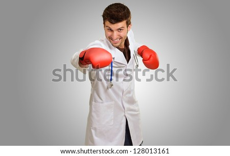 Young Doctor Wearing Boxing Gloves On Grey Background - stock photo