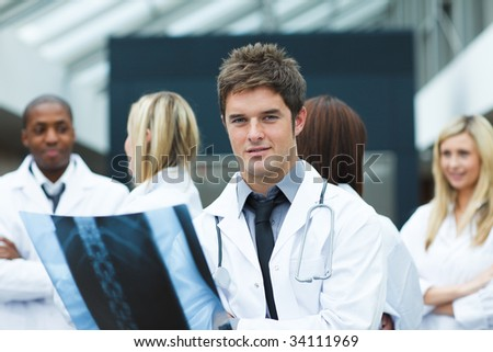 Young doctor with an x-ray looking at the camera and his team in the background - stock photo