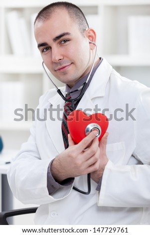 Young doctor with heart and stethoscope - stock photo