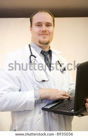 Young doctor with laptop smiling - stock photo