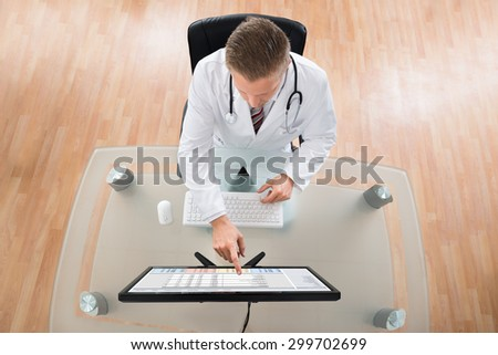 Young Doctor With Stethoscope Using Computer At Desk - stock photo