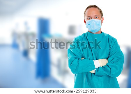young doctor with surgical mask and green coat - stock photo