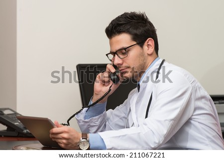 Young Doctor Working At His Computer While Talking On The Phone - stock photo