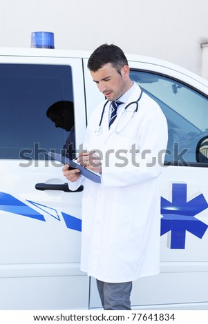 young doctor writing in front of ambulance - stock photo