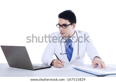 Young doctor writing notes with a notebook at the desk, isolated on white