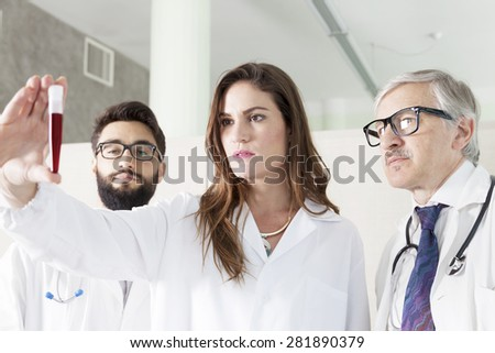 young doctors examines blood tube in laboratory - stock photo