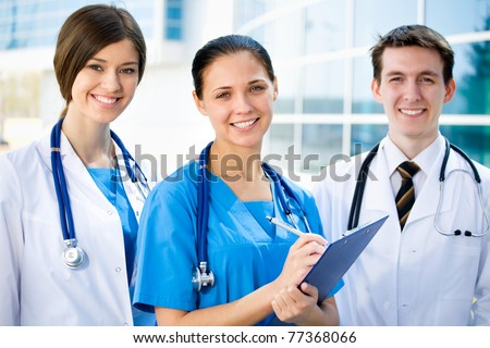 Young doctors standing against a hospital building - stock photo