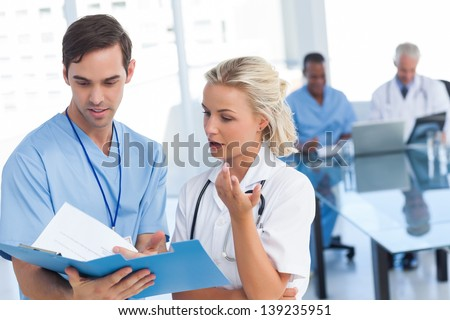 Young doctors talking about a blue file in a meeting room - stock photo