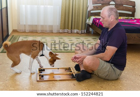 Young dog and mature man playing backgammon - stock photo