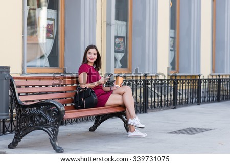 Young dreaming female holding cell telephone while sitting on bench in the fresh air, attractive brunette woman chatting on her smart phone in urban setting, gorgeous hipster girl using technology  - stock photo