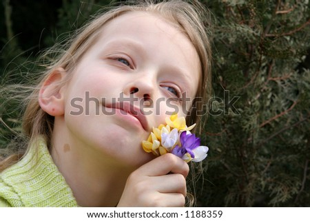 Young, dreaming girl with a bunch of crocuses