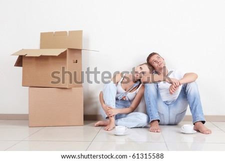 Young dreams of a couple drinking coffee in the new apartment - stock photo