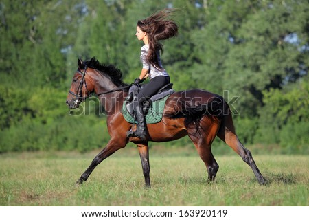 Young dressage girl on full blood horse galloping