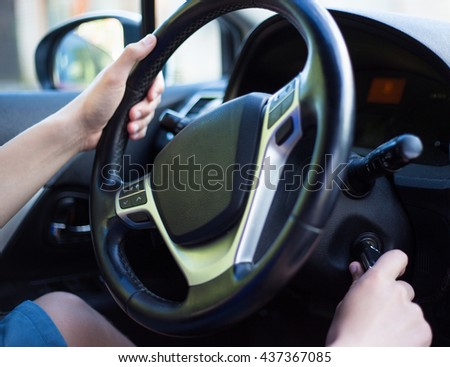 young driver's hand holding car key for starting the car - stock photo