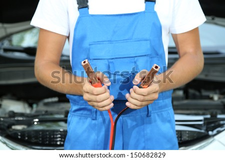 Young driver with battery jumper cables to charge dead battery - stock photo