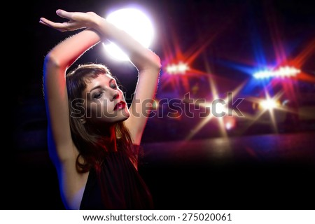 young drug or alcohol intoxicated female holding her hands up while being arrested. she is dressed like she came from a party and police cars in the background. - stock photo