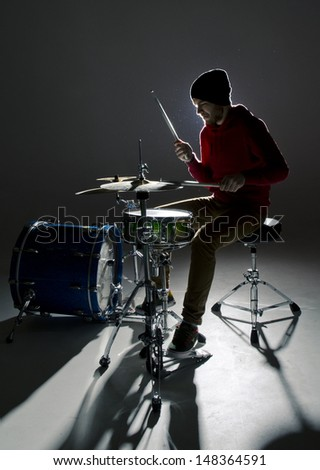 young drummer playing in the contre light - stock photo