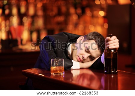 Young drunk man sleeping in the bar, with glass of whiskey in his hand - stock photo