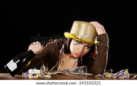 Young drunk woman sitting by a desk with empty champagne bottle after celebrating new years eve. On black background. - stock photo