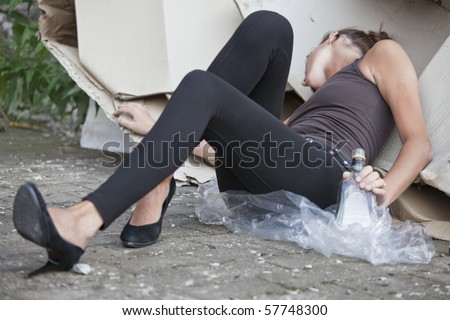 young drunk woman with bottle in her hand sleeping outdoor - stock photo