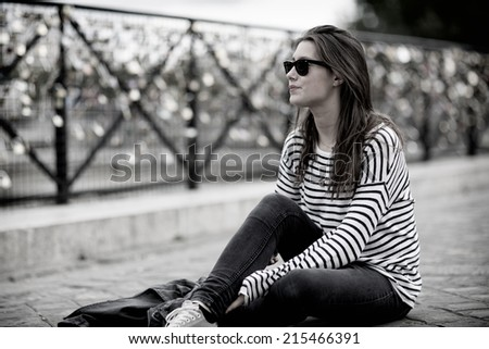 Young Dutch woman in black and white sitting in front of thousands of locks hung up at the side of a bridge in Paris, capital of France, as a sign of eternal love - stock photo