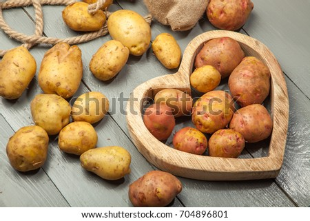 Young early potatoes in an old metal bowl on a wooden background.