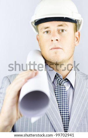 Young electrical engineer wearing a safety hard hat walking to the construction site carrying his blueprint drawings - stock photo